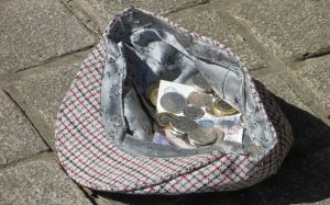 a hat on the ground with coins and banknotes